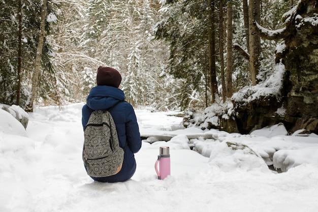 バックパックと魔法瓶を持つ少女は、雪に覆われた針葉樹林に座っています。