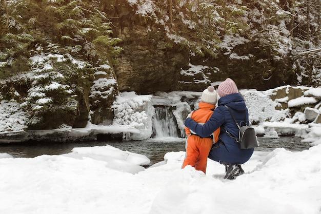 ママと息子の雪の背景に抱擁で座っています。