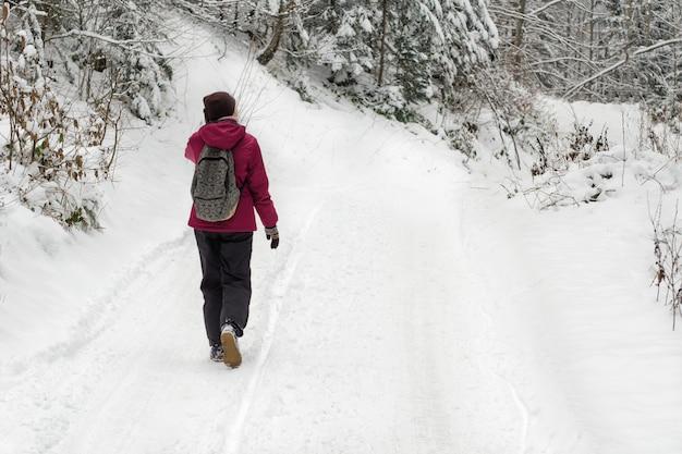 Девушка с рюкзаком, прогуливаясь по дороге в снежном лесу.