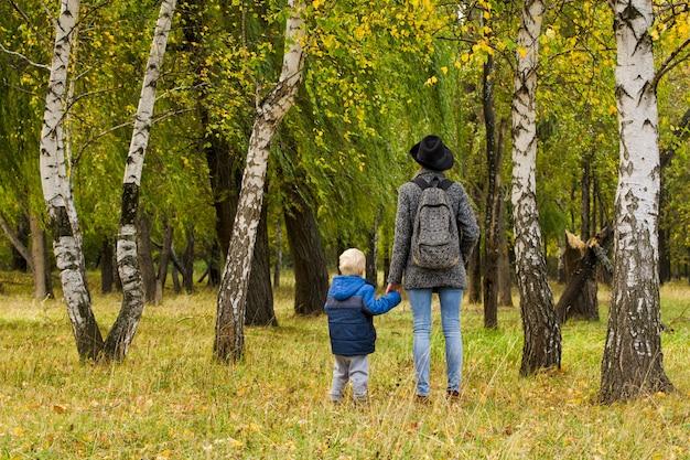 ママと息子は秋の森を歩いています。