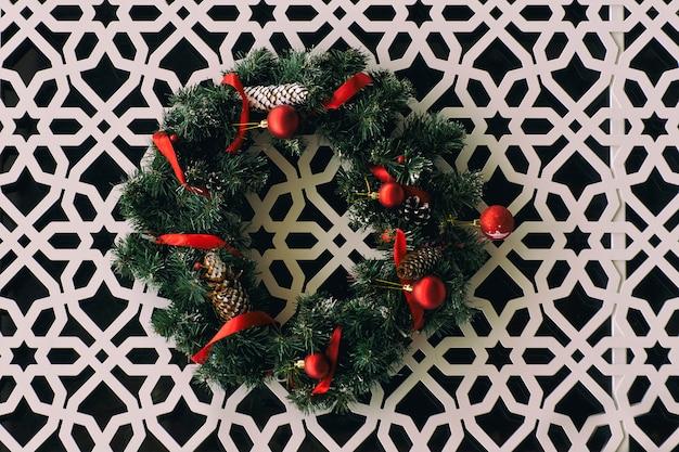 彫刻が施された飾りと白い壁に掛かっている赤いリボンとクリスマスリース