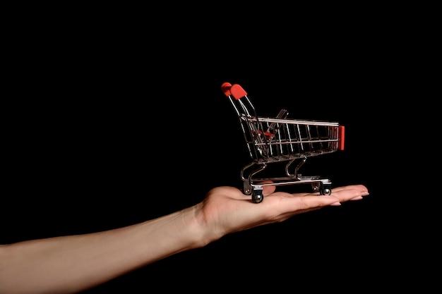 暗闇の中で女性の手のひらにショッピングトロリー