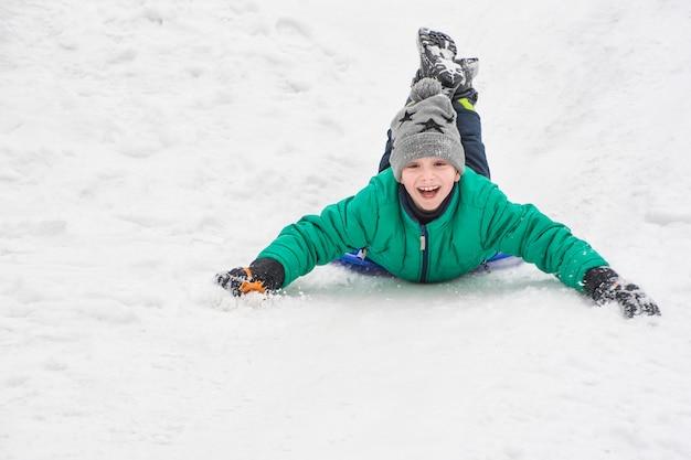 Смеющийся мальчик едет по животу с горки на снежной тарелке.