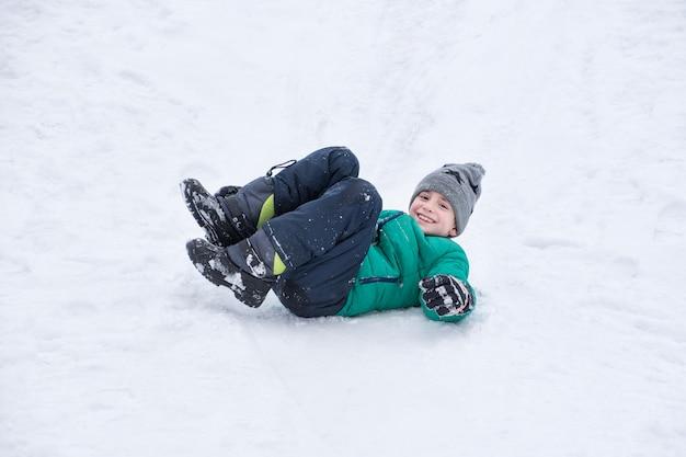 Мальчик падает катится по снежной горке.