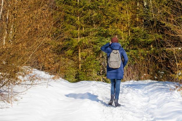 Девушка с рюкзаком стоял в снежном лесу.