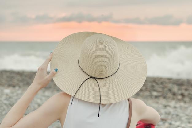 海のそばに座っている帽子の少女