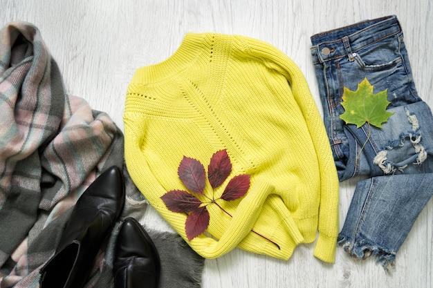黄色いセーター、スカーフ、ジーンズ、靴。