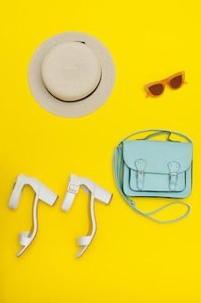 女性のビーチハット、ハンドバッグ、白い靴。黄色の背景