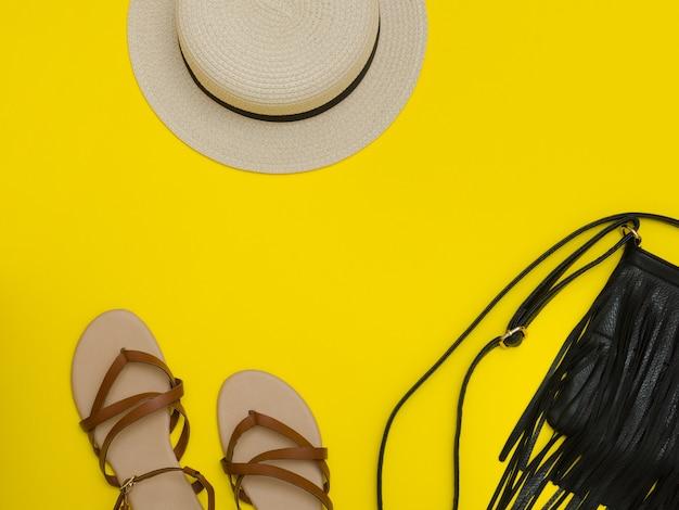 女性のビーチ帽子、ハンドバッグ、サンダル。黄色の背景