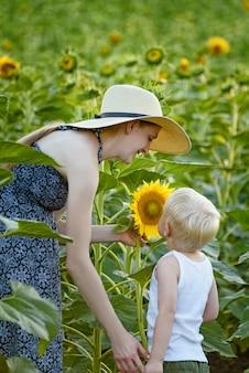 Мама и маленький сын стоят и вдыхают аромат подсолнуха