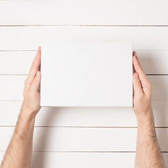 Белая прямоугольная коробка в мужских руках. вид сверху.