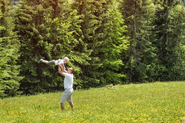 父は緑の牧草地で赤ちゃんの息子をスローします