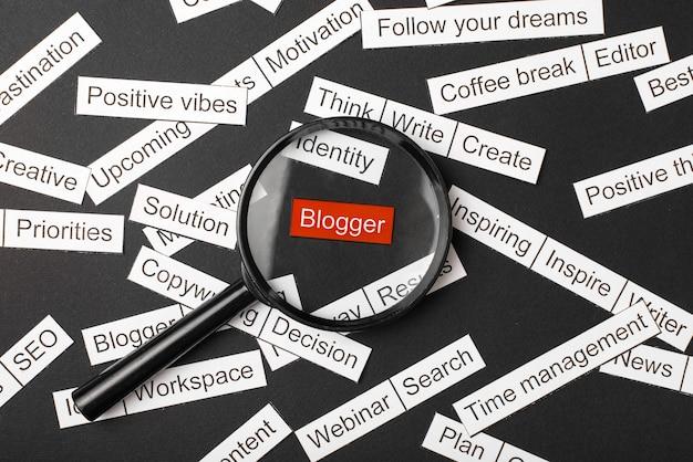 Стекло лупы над красной надписью блоггера вырезано из бумаги