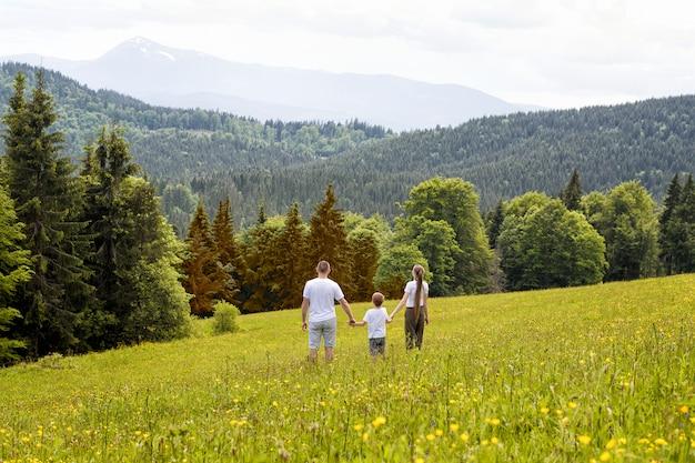 Отец с маленьким сыном и матерью стоят рука об руку на зеленом поле