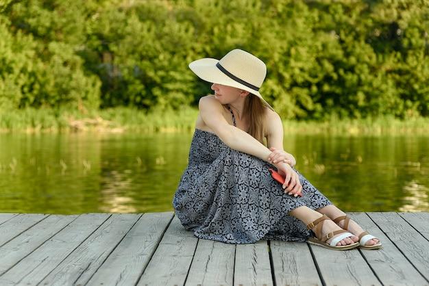 Красивая девушка в шляпе и платье сидит на пирсе у реки
