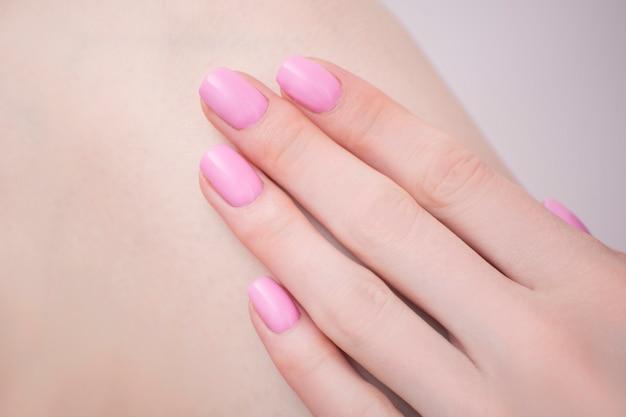 ピンクのマニキュアで女性の手。閉じる。マニキュアサロン