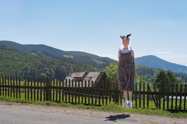 ドレスで美しい幸せなブルネットの少女がバウンス