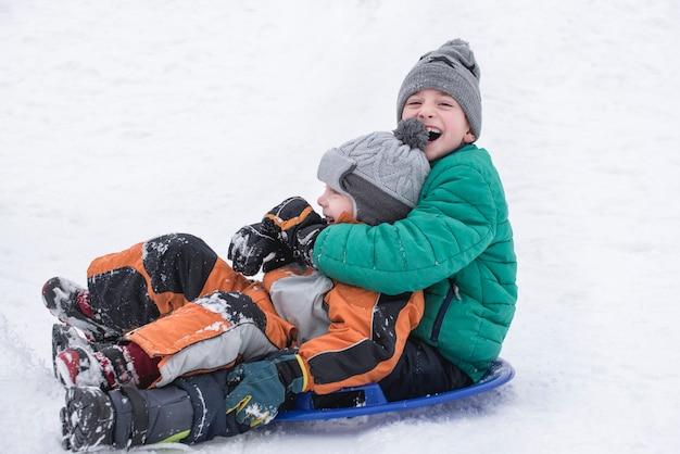Два радостных мальчика спускаются с горки на снежной тарелке.