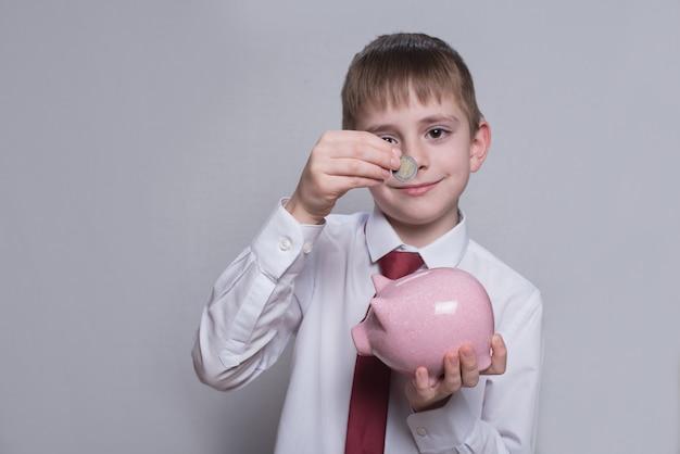 微笑む少年は、ピンクの貯金箱にコインを置きます。事業コンセプト。