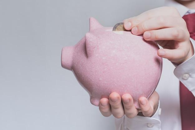 子供の手はピンクの貯金箱にコインを入れます。事業コンセプト。閉じる