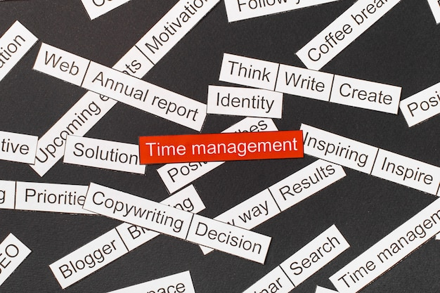 Вырежьте бумажные надписи тайм-менеджмента на красном фоне, в окружении других надписей на темном фоне облако слов
