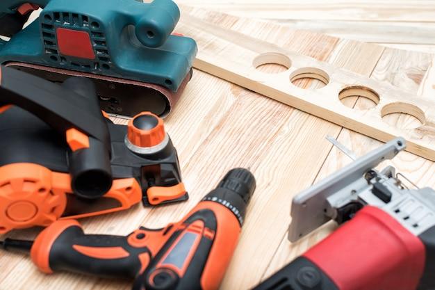 Набор ручных деревообрабатывающих электроинструментов для деревообработки и заготовки лежит на светлом деревянном. закрыть