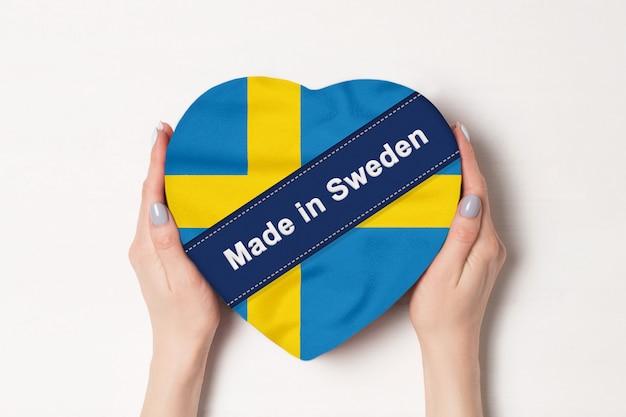 Надпись сделано в швеции флаг швеции. женские руки, держа коробку в форме сердца.
