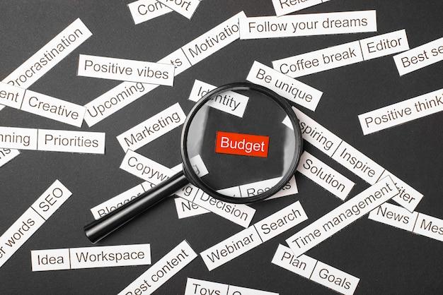 Стекло лупы над красной надписью бюджета вырезано из бумаги. в окружении других надписей на темном фоне. слово облако концепции.
