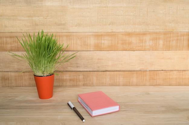 木製のテーブルにメモ帳とペン。緑の観葉植物