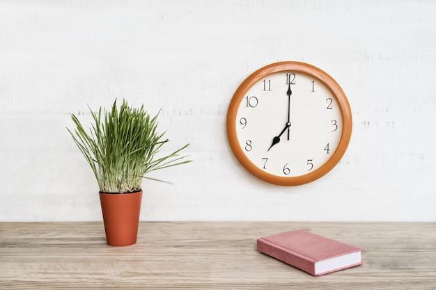 Круглые настенные часы, розовый блокнот на столе и зеленое комнатное растение