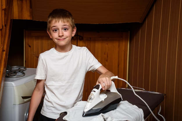 Школьник гладит свою одежду электрическим утюгом