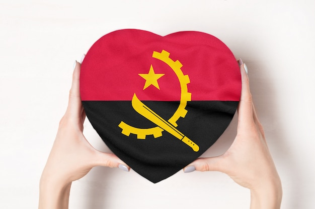 女性の手でハート形ボックスにアンゴラの旗。白色の背景