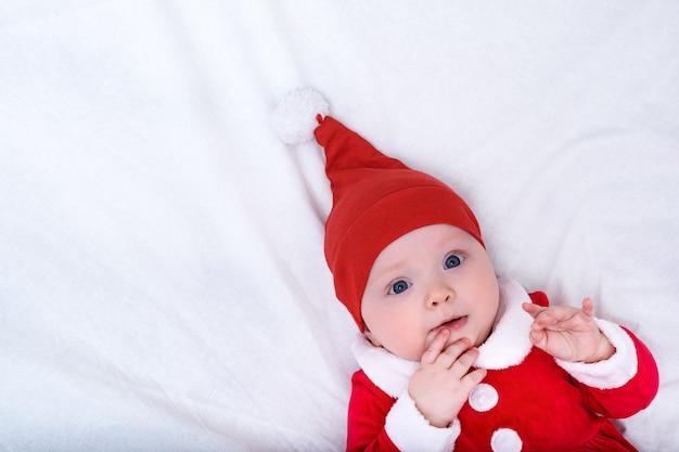 サンタの帽子と衣装でかわいい女の子の肖像画。クリスマスのコンセプト。コピースペース。白色の背景。