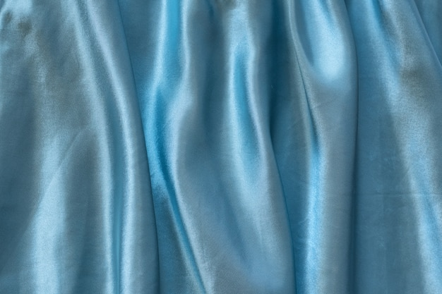 青い絹のしわ生地。テクスチャ背景