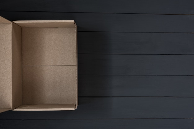 Пустая открытая картонная коробка на черном деревянном фоне