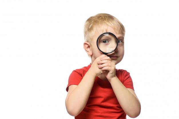 彼の手に虫眼鏡を持つ金髪の少年。小さな探検家。白色の背景