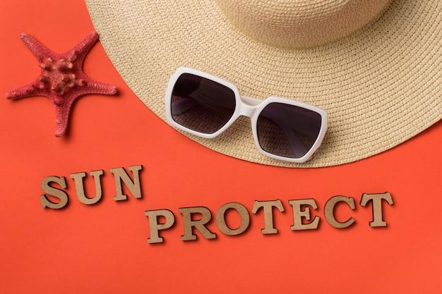 単語の太陽は木製の手紙から保護します。サングラス、帽子の一部、ヒトデ。サンゴのライブ背景。旅行