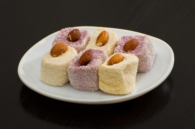 Бело-фиолетовый рахат-лукум с миндалем на белом блюде, черный