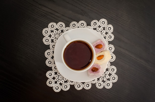 Кофейная кружка на блюдце с рахат-лукумом на черном столе, вид сверху