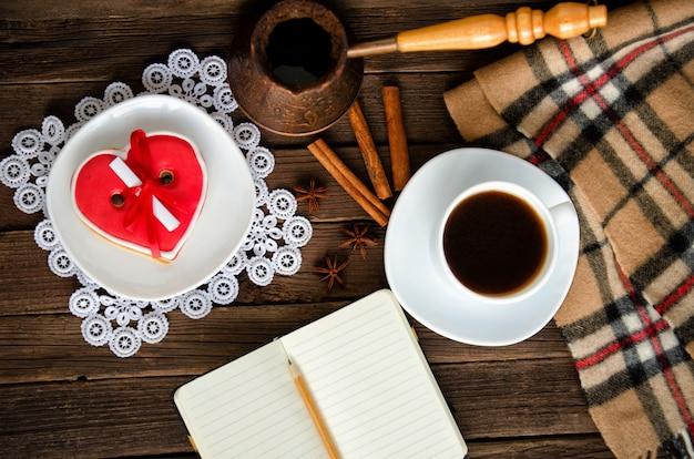 Уютный отдых. кружка для кофе, пряники в форме сердца, блокнот и карандаш, плед и специи. вид сверху
