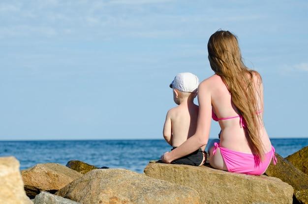母と息子が海岸の岩の上に座って
