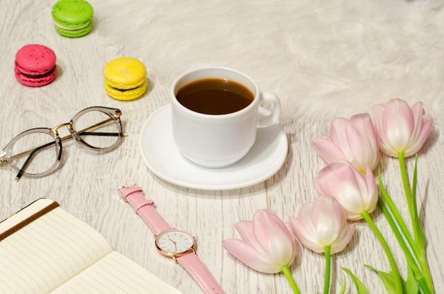 コーヒーマグ、サングラス、時計、ノート、テーブルの上のピンクのチューリップ。働くコンセプト。