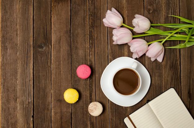 一杯のコーヒー、マカロン、ピンクのチューリップ、木製の背景上のノートブック。