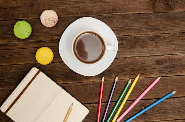 コーヒーマグ、マカロン、色鉛筆、木製の背景にメモ帳