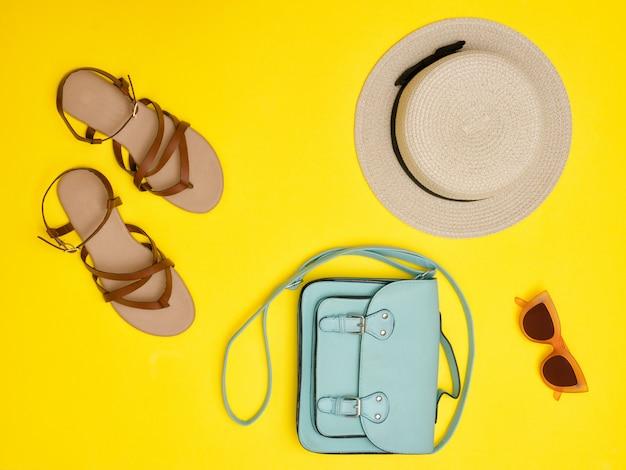 ファッショナブルなコンセプト。女性用の麦わら帽子、ミントのハンドバッグ、サングラス、サンダル