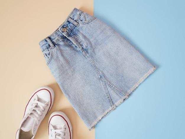 ファッショナブルなコンセプト。女性の都会的なスタイル。デニムスカートと淡い青の背景に白いスニーカー、ベージュ