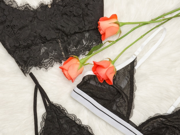 Детали черного кружевного бюстгальтера на белом меху и оранжевых розах. модная концепция. вид сверху. крупный план