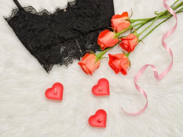 Черный кружевной бюстгальтер на белом меху, оранжевые розы, свечи. модная концепция. вид сверху. крупный план