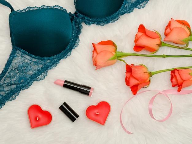 Детали изумрудного лифа с кружевом. оранжевые розы, помада, свечи в форме сердца. модная концепция. вид сверху