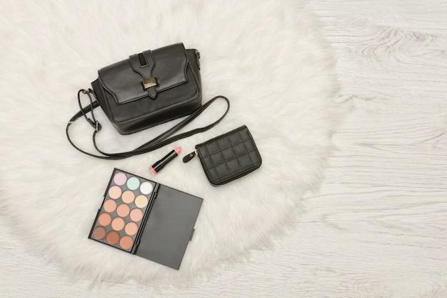 黒いハンドバッグ、アイシャドウ、財布、口紅。白い毛皮、トップビュー。ファッショナブルなコンセプト